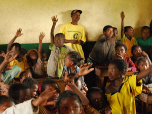 Classroom of children with their hands up