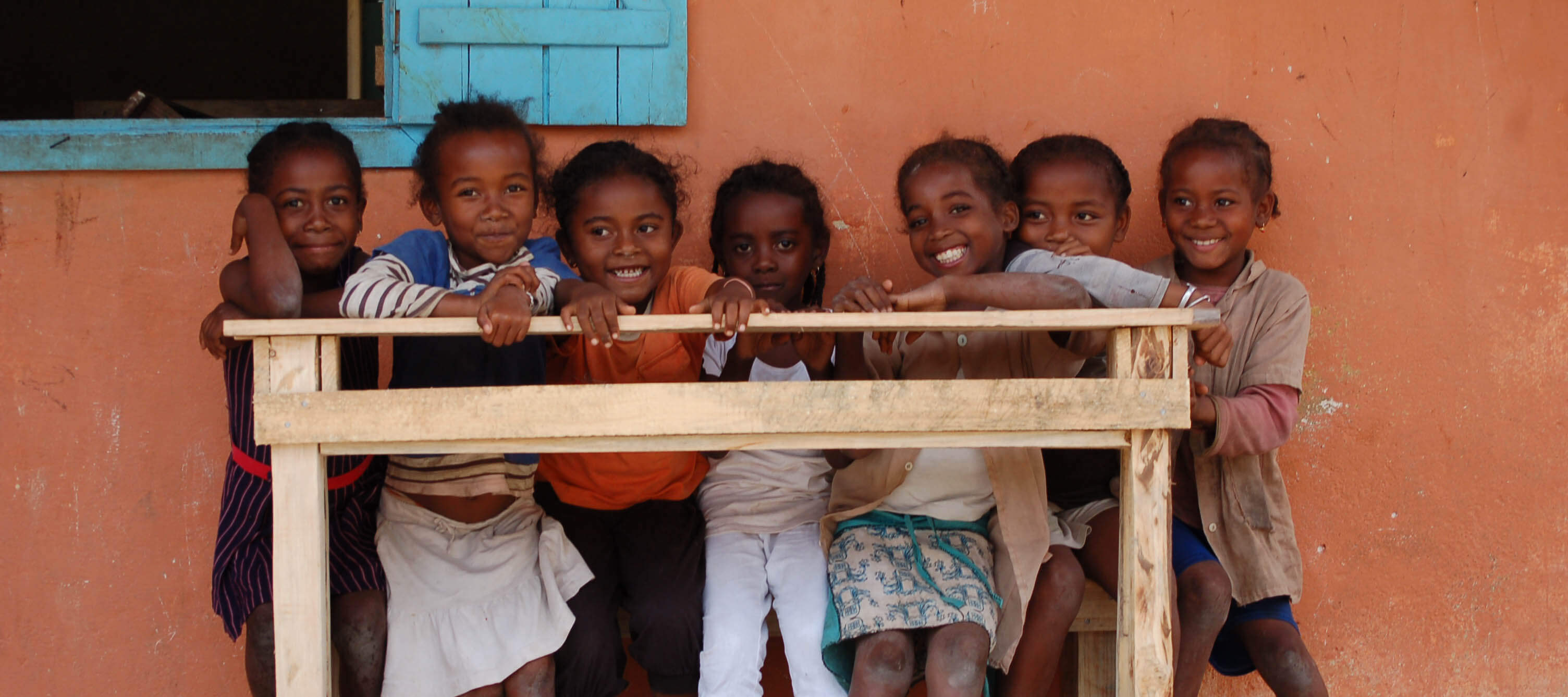 Photo of laughing children carrying a newly-finished bench to school