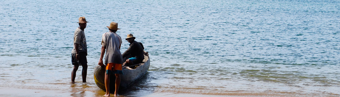 Malagasy men with a traditional wooden canoe, or pirogue