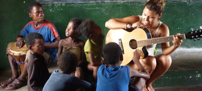 A volunteer plays guitar with local children