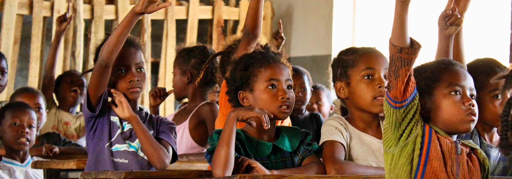 Malagasy children in school classroom with hands up