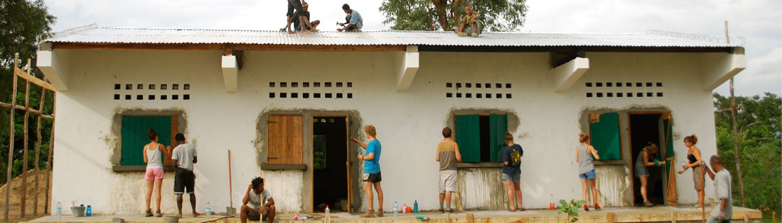 Photo of volunteers painting a concrete schoolbuilding.