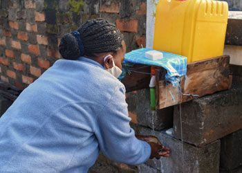 Vayah using the new handwashing system at the SEED office