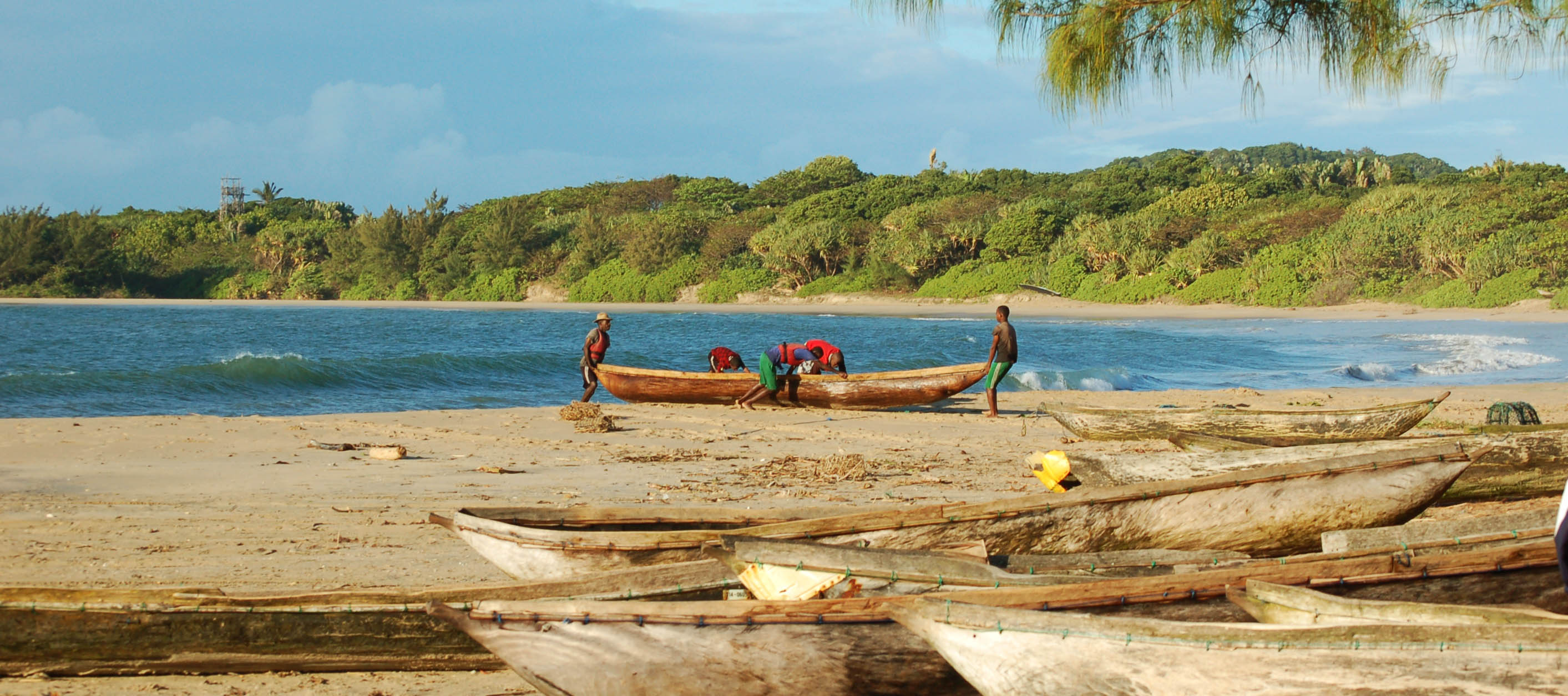 Fishermen push a wooden pirogue into the sea